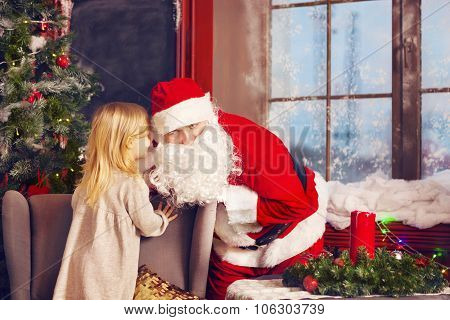 Little Girl Telling Her Christmas Wish In Santa Claus Near The Christmas Tree
