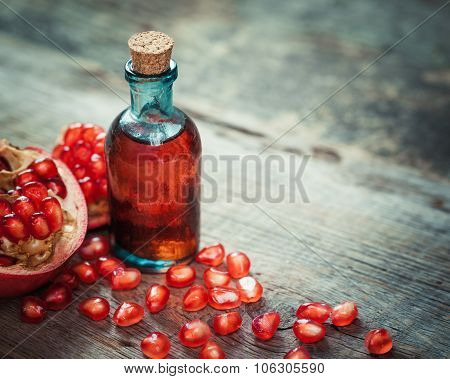 Pomegranate Juice Or Tincture And Garnet Fruit With Seeds On Kitchen Table.