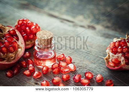 Pomegranate Oil In Bottle And Garnet Fruit With Seeds On Table.