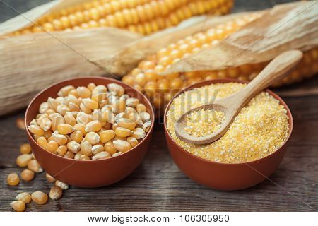 Corn Grits And Seeds In Bowls, Corncobs On Kitchen Table.