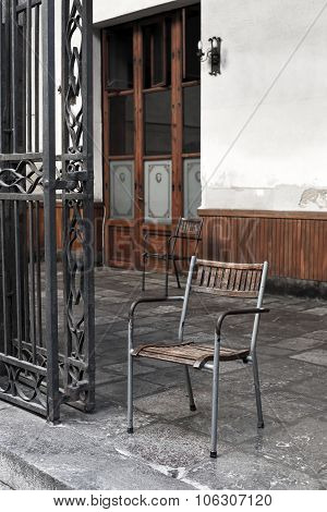 Vintage Wooden And Iron Chair In A Porch.