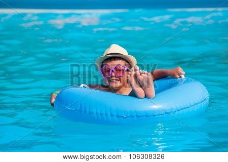 Boy with hat, glasses in inflatable ring swimming