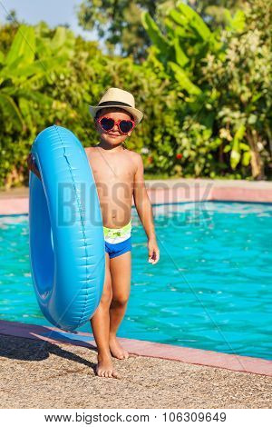 Cute small boy in hat holding inflatable ring