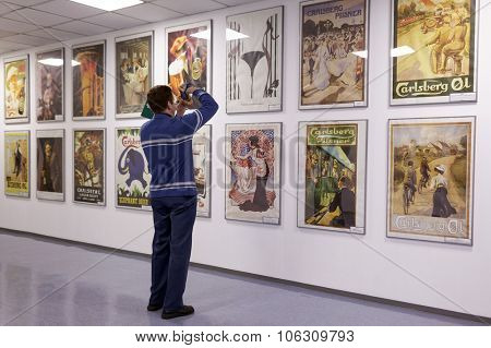 ST. PETERSBURG, RUSSIA - OCTOBER 24, 2015: Tourist making photo of beer posters at the Baltika - St Petersburg brewery during the October Beer Festival. The brewery provides guided tours to the plant