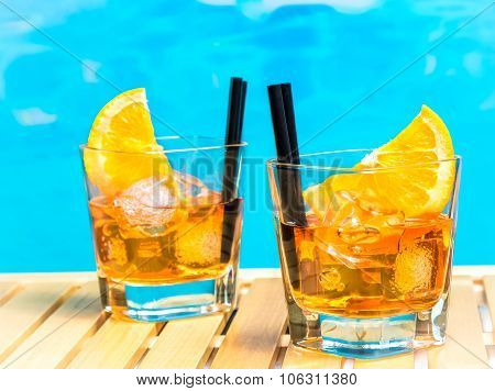 Two Glasses Of Spritz Aperitif Aperol Cocktail With Orange Slices And Ice Cubes On Swimming Pool Bac