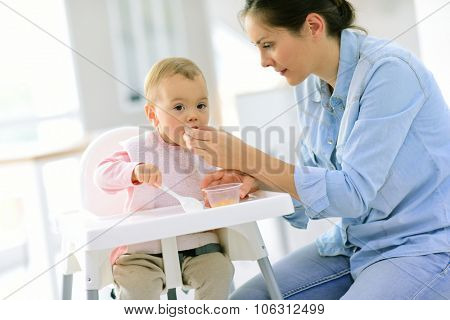 Baby girl eating in her chair, mommy by her side