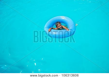 Happy small boy in inflatable ring swimming alone