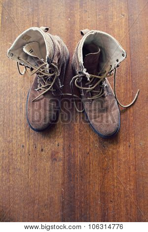 Overhead Of Worn Old Work Boots On Wooden Floor