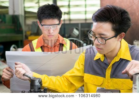 Asian Mechanical Engineer Checking Equipment In Factory