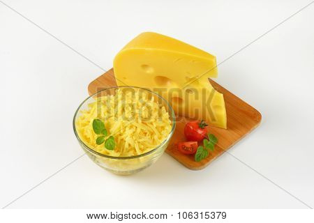 bowl of grated cheese and cheese wedge on wooden cutting board