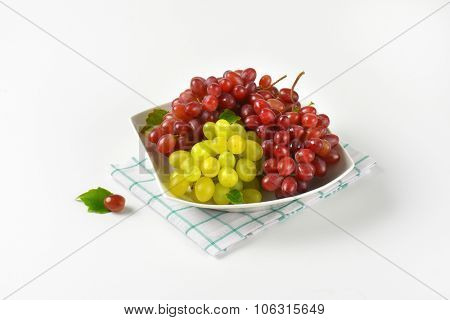 bowl of red and white grapes on checkered dishtowel