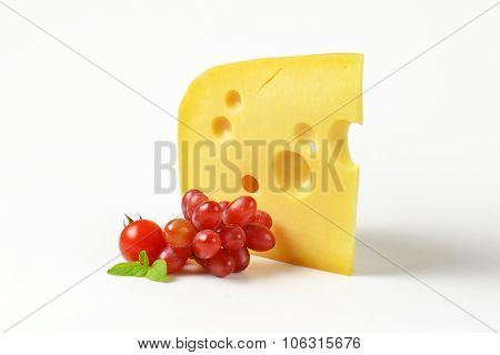 wedge of fresh cheese with red grapes on white background