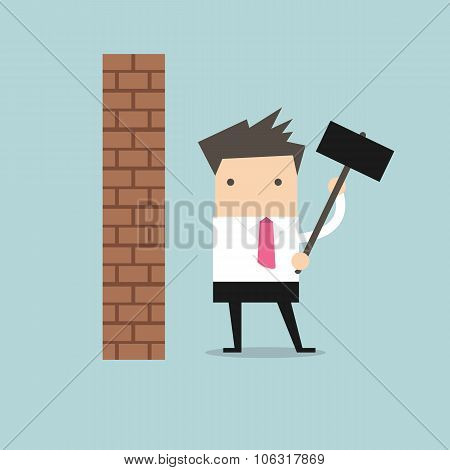 Businessman breaking wall with hammer