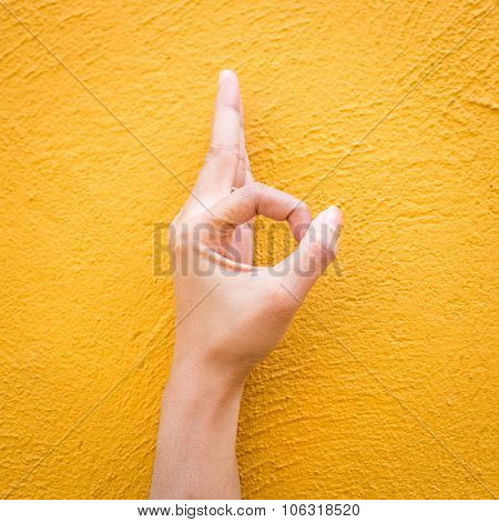 Woman Hand In Ok Sign On Cement Yellow Wall Background