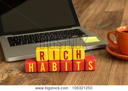 Rich Habits written on a wooden cube in front of a laptop