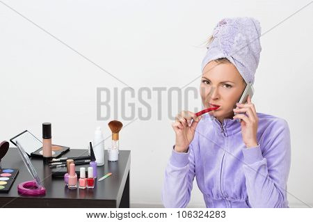 woman brushing her teeth and talking on the phone