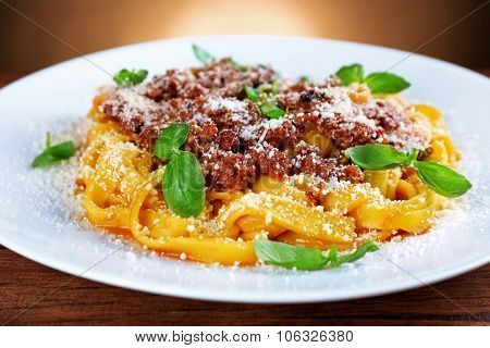 Pasta Bolognese with parmesan and basil on dark background