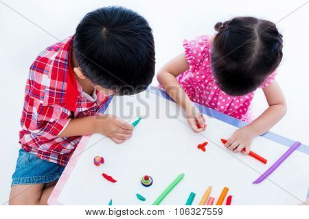Top View. Asian Kids Playing With Play Clay On Table. Strengthen The Imagination
