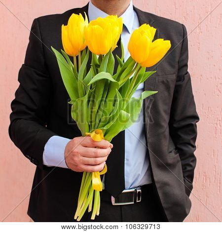 A man wearing business suit, holding bouquet of yellow tulips.