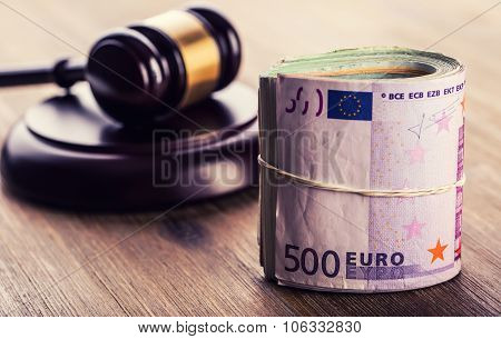 Judge's hammer gavel. Justice and euro money. Euro currency. Court gavel and rolled Euro banknotes.