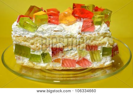 Appetizing Jelly cake on transparent dish on a yellow background