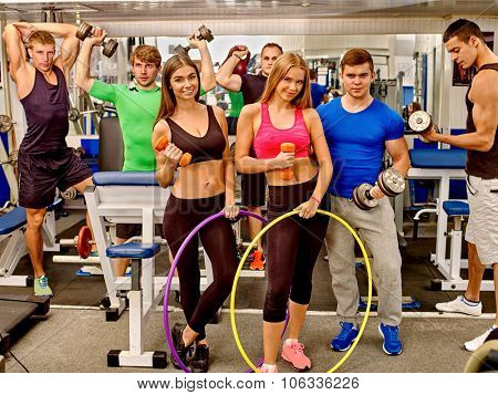 Group of men and happy women trained in the gym using the equipment, dumbbells and fitnes hoop. Group portrait.