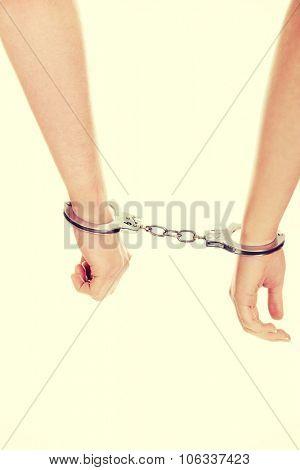 Young beautiful caucasian couple handcuffed.
