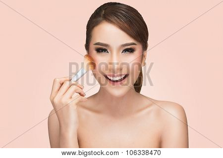portrait of asian woman applying dry cosmetic tonal foundation on the face