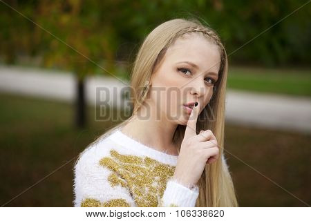 Portrait of attractive girl with finger on lips, concept of student show quiet, silence, secret gesture, young pretty blonde woman