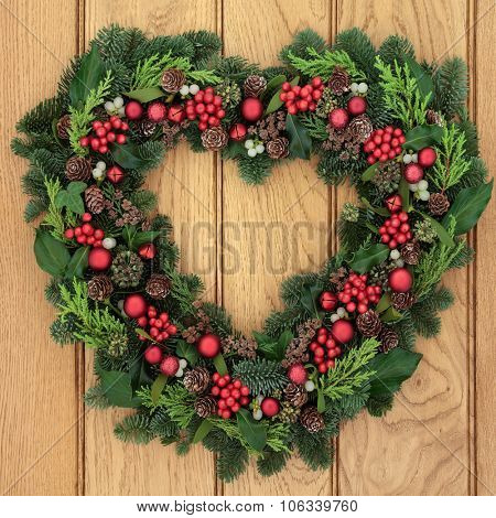 Christmas and winter heart shaped wreath with holly, mistletoe, red bauble decorations and greenery over oak front door background.