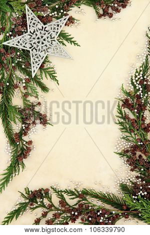 Christmas background border with silver star and ball decorations, fir and cedar cypress leaf sprigs over old parchment paper.