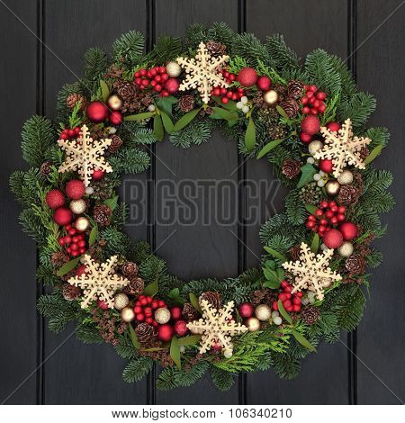 Christmas wreath with gold snowflake bauble decorations, holly, mistletoe and winter greenery over dark oak front door background.