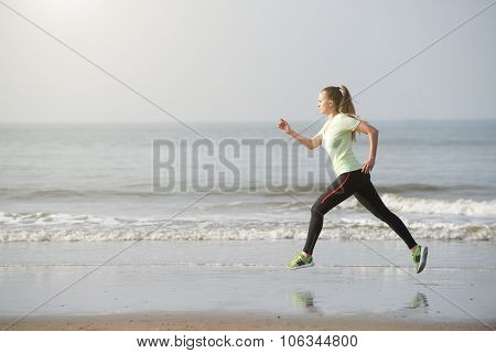 Healthy Young Woman Running By The Beach