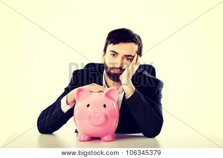 Worried businessman with piggybank by a desk.