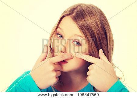 Teenage worried woman squeezing pimple