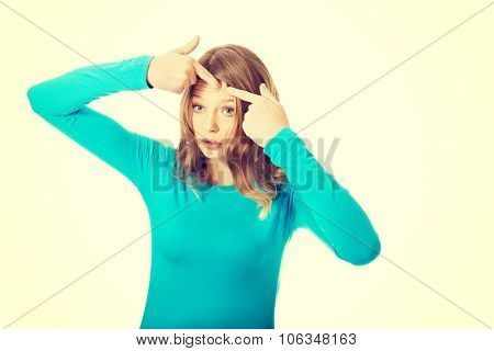 Worried teenage woman squeezing pimple