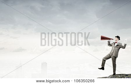Young businessman on rock top screaming emotionally in paper trumpet