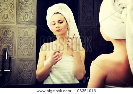 Attractive woman applying parfume in the bathroom.