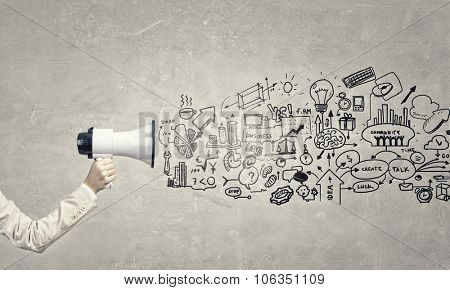 Hand of businesswoman with megaphone and business strategy sketches