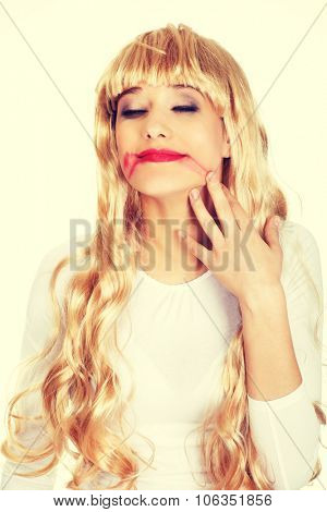 Sad blonde woman with smeared red lipstick.
