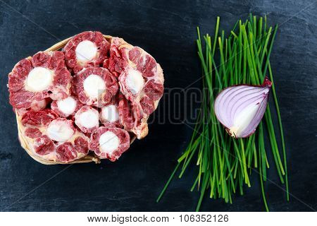 Fresh Raw Beef Oxtail Meat Cut, Ready To Cook. With Vegetable. On Blue Stone  Background.