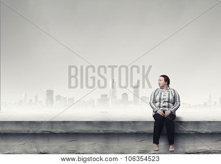 Middle aged stout woman sitting on building roof