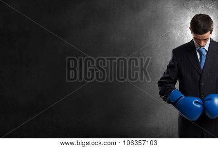 Young businessman in blue boxing gloves on dark background