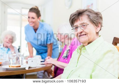 Group of seniors having food in nursing home, a nurse is serving