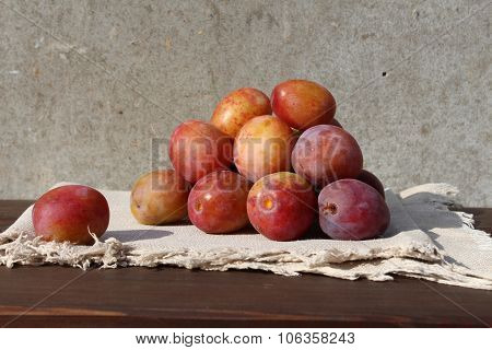 Small group of plums on the wood table.