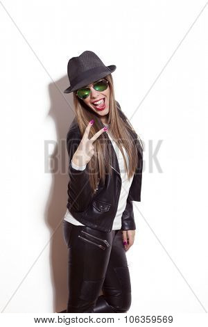 young blonde woman making faces and gestures, wearing sunglasses hat black leather jacket and leggings, studio white
