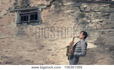 Young man playing saxophone near window of old house