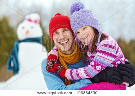 Father and daughter with snowman
