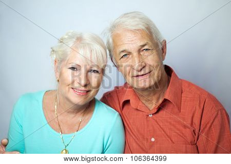 Senior couple smiling for a portrait and looking happy