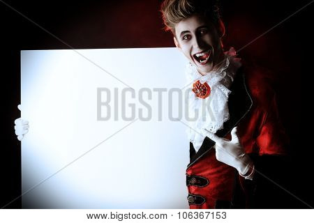 Bewitching handsome male vampire holding a billboard with copy space. Halloween. Dracula costume.